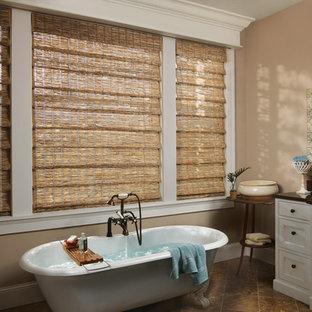Immagine di una stanza da bagno tradizionale con lavabo sottopiano, ante con riquadro incassato, ante bianche, vasca con piedi a zampa di leone, piastrelle marroni e pareti beige