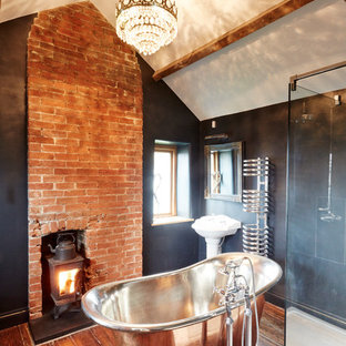 This is an example of a medium sized rural ensuite bathroom in Wiltshire with a pedestal sink, a freestanding bath, a wall mounted toilet, medium hardwood flooring and black walls.