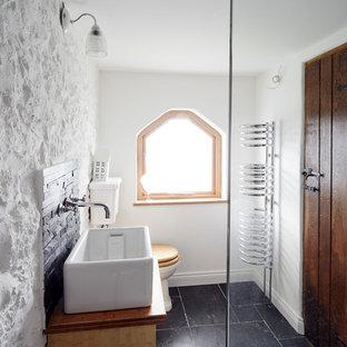 Ejemplo de cuarto de baño rústico, pequeño, con lavabo de seno grande, encimera de madera, sanitario de dos piezas, baldosas y/o azulejos negros, baldosas y/o azulejos de piedra, paredes blancas, suelo de piedra caliza y encimeras marrones