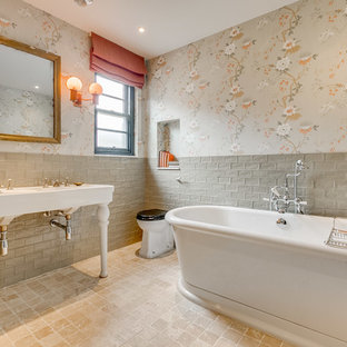 Photo of a medium sized classic ensuite bathroom in London with a freestanding bath, grey tiles, stone tiles, a console sink, beige floors, white worktops and a one-piece toilet.