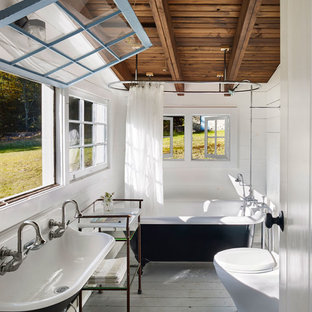 Example of a farmhouse master painted wood floor bathroom design in New York with white walls and a trough sink