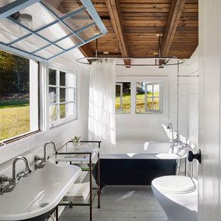 Cette image montre une salle de bain principale rustique avec une baignoire sur pieds, un combiné douche/baignoire, un mur blanc, un sol en bois peint, une grande vasque et une cabine de douche avec un rideau.