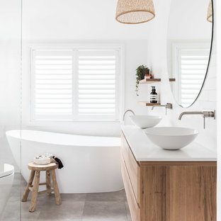 Design ideas for a contemporary master bathroom in Sydney with flat-panel cabinets, medium wood cabinets, a freestanding tub, a curbless shower, a one-piece toilet, white tile, white walls, porcelain floors, a vessel sink, grey floor, an open shower, white benchtops, porcelain tile, engineered quartz benchtops, a double vanity and a floating vanity.