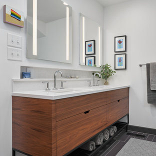 Example of a trendy black floor and double-sink bathroom design in Minneapolis with flat-panel cabinets, medium tone wood cabinets, white walls, an undermount sink and white countertops