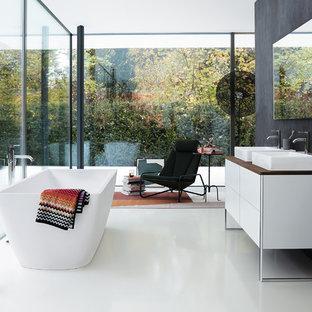 Cette photo montre une salle de bain moderne avec un placard à porte plane, des portes de placard blanches, un mur noir, une vasque, un plan de toilette en bois, un sol blanc et un plan de toilette marron.