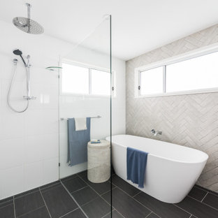 Inspiration for a beach style bathroom in Gold Coast - Tweed with a freestanding tub, a curbless shower, gray tile, black floor and an open shower.