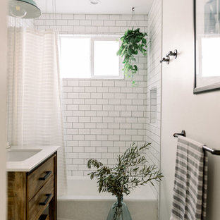 Inspiration for a small farmhouse family bathroom in San Diego with flat-panel cabinets, medium wood cabinets, a corner bath, an alcove shower, a two-piece toilet, white tiles, metro tiles, white walls, porcelain flooring, a console sink, engineered stone worktops, black floors, a shower curtain and white worktops.