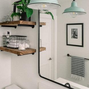 Inspiration för ett litet lantligt vit vitt badrum för barn, med släta luckor, skåp i mellenmörkt trä, ett hörnbadkar, en dusch i en alkov, en toalettstol med separat cisternkåpa, vit kakel, tunnelbanekakel, vita väggar, klinkergolv i porslin, ett konsol handfat, bänkskiva i kvarts, svart golv och dusch med duschdraperi