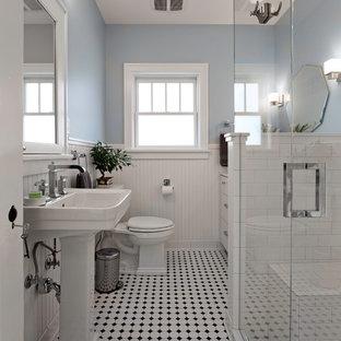 他の地域のヴィクトリアン調のおしゃれな浴室 (ペデスタルシンク、フラットパネル扉のキャビネット、白いキャビネット、分離型トイレ、白いタイル、サブウェイタイル、青い壁、セラミックタイルの床、マルチカラーの床) の写真