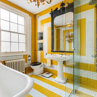 Immagine di una stanza da bagno padronale eclettica con zona vasca/doccia separata, WC sospeso, piastrelle multicolore, piastrelle bianche, piastrelle gialle, pareti multicolore, lavabo a colonna, pavimento multicolore, vasca ad angolo e piastrelle in ceramica