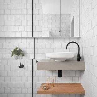 Exempel på ett litet minimalistiskt badrum, med öppna hyllor, skåp i ljust trä, en kantlös dusch, vit kakel, tunnelbanekakel, vita väggar, mosaikgolv, ett väggmonterat handfat, dusch med gångjärnsdörr och bänkskiva i akrylsten