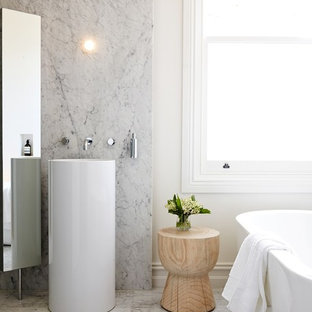 Inspiration for a mid-sized contemporary marble tile and gray tile marble floor and white floor freestanding bathtub remodel in Melbourne with white walls and a console sink