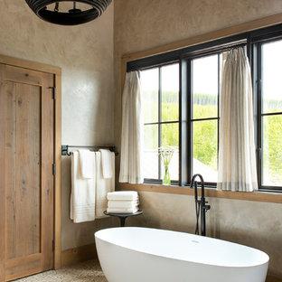 Modelo de cuarto de baño principal, rural, de tamaño medio, con bañera exenta, paredes beige, suelo con mosaicos de baldosas y suelo beige