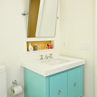 Ejemplo de cuarto de baño costero con lavabo bajoencimera, armarios con paneles lisos, puertas de armario azules, baldosas y/o azulejos amarillos y baldosas y/o azulejos de cemento