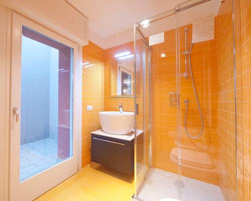 Bagno con piastrelle arancioni e pareti gialle foto idee