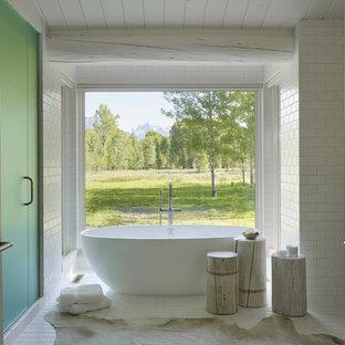 Ejemplo de cuarto de baño rural con bañera exenta, baldosas y/o azulejos blancos y baldosas y/o azulejos de cemento