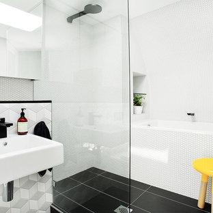 Imagen de cuarto de baño actual con lavabo suspendido, ducha a ras de suelo, baldosas y/o azulejos blancos, baldosas y/o azulejos en mosaico, bañera encastrada y suelo negro