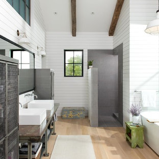 Example of a farmhouse master light wood floor and beige floor bathroom design in Other with open cabinets, white walls and a vessel sink