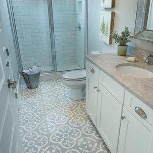 Exemple d'une grande salle de bain nature avec un placard avec porte à panneau encastré, des portes de placard blanches, une douche double, un carrelage gris, un mur gris, un sol en carrelage de céramique et un lavabo encastré.
