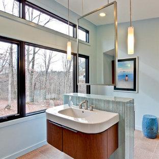Foto de cuarto de baño principal, moderno, grande, con lavabo integrado, armarios con paneles lisos, baldosas y/o azulejos azules, baldosas y/o azulejos de porcelana, puertas de armario de madera en tonos medios, paredes grises, suelo de baldosas de porcelana y encimera de acrílico
