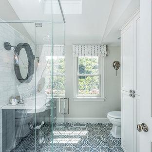 Ejemplo de cuarto de baño con ducha, clásico renovado, de tamaño medio, con puertas de armario negras, ducha esquinera, sanitario de una pieza, baldosas y/o azulejos grises, baldosas y/o azulejos de piedra, paredes grises, suelo de azulejos de cemento, lavabo bajoencimera, encimera de cuarcita, suelo azul y ducha con puerta con bisagras