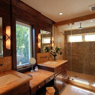Imagen de sauna de estilo americano, grande, con lavabo bajoencimera, armarios con paneles con relieve, puertas de armario de madera oscura, encimera de piedra caliza, sanitario de una pieza, baldosas y/o azulejos beige, suelo de baldosas tipo guijarro y suelo de piedra caliza