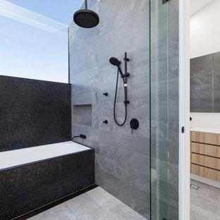 Ejemplo de cuarto de baño principal, actual, de tamaño medio, con puertas de armario de madera oscura, bañera encastrada, baldosas y/o azulejos grises, baldosas y/o azulejos negros, baldosas y/o azulejos de porcelana, paredes blancas, suelo de baldosas de porcelana, encimera de laminado, suelo gris, ducha abierta, armarios con paneles lisos, combinación de ducha y bañera, lavabo bajoencimera y encimeras blancas
