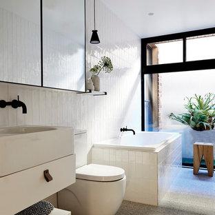 Mittelgroßes Modernes Badezimmer mit profilierten Schrankfronten, Eckbadewanne, Wandtoilette mit Spülkasten, weißen Fliesen, Porzellanfliesen, weißer Wandfarbe, Keramikboden und Mineralwerkstoff-Waschtisch in Melbourne