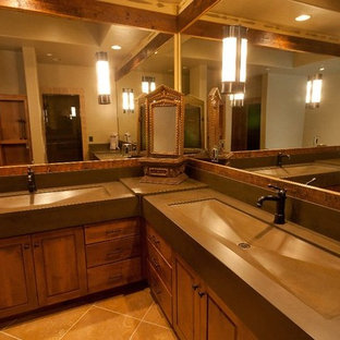 他の地域の大きいラスティックスタイルのおしゃれなマスターバスルーム (一体型シンク、コンクリートの洗面台、ドロップイン型浴槽、ベージュのタイル、石タイル) の写真