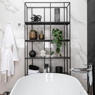 Idéer för ett stort modernt svart en-suite badrum, med släta luckor, skåp i mellenmörkt trä, ett fristående badkar, en toalettstol med hel cisternkåpa, vit kakel, vita väggar, ett fristående handfat, brunt golv, dusch med gångjärnsdörr, en hörndusch, stenhäll, mellanmörkt trägolv och bänkskiva i akrylsten