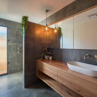 Idéer för ett mellanstort modernt brun en-suite badrum, med släta luckor, skåp i mellenmörkt trä, keramikplattor, klinkergolv i keramik, ett fristående handfat, träbänkskiva, grått golv, med dusch som är öppen, en kantlös dusch och grå kakel