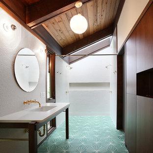 Modelo de cuarto de baño con ducha, retro, con lavabo bajoencimera, armarios con paneles lisos, puertas de armario de madera en tonos medios, ducha doble, baldosas y/o azulejos blancos y suelo turquesa