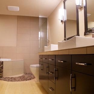 Ejemplo de cuarto de baño asiático con lavabo sobreencimera, bañera encastrada, ducha a ras de suelo, armarios con paneles lisos, puertas de armario negras, encimera de azulejos, sanitario de una pieza, baldosas y/o azulejos beige y baldosas y/o azulejos de porcelana
