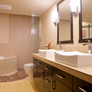 Imagen de cuarto de baño asiático con lavabo sobreencimera, armarios con paneles lisos, puertas de armario negras, encimera de azulejos, bañera encastrada, ducha a ras de suelo, sanitario de una pieza, baldosas y/o azulejos beige y baldosas y/o azulejos de porcelana