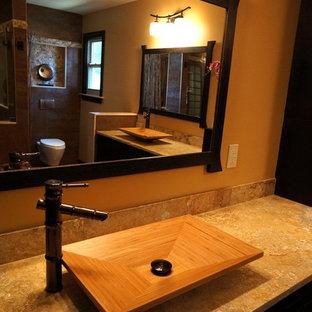 Ejemplo de cuarto de baño principal, asiático, de tamaño medio, con armarios con paneles con relieve, puertas de armario negras, ducha empotrada, sanitario de pared, paredes marrones, suelo de pizarra, lavabo sobreencimera y encimera de piedra caliza