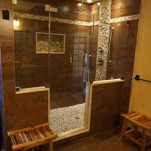 Imagen de cuarto de baño principal, asiático, de tamaño medio, con armarios con paneles con relieve, puertas de armario negras, ducha empotrada, sanitario de pared, paredes marrones, suelo de pizarra, lavabo sobreencimera y encimera de piedra caliza
