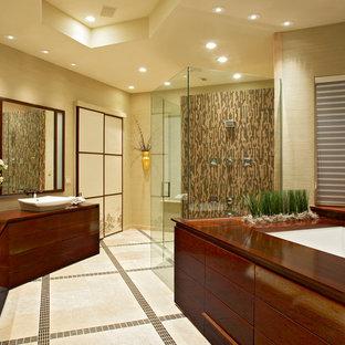 Неиссякаемый источник вдохновения для домашнего уюта: большая главная ванная комната в восточном стиле с душем без бортиков, полом из травертина, столешницей из дерева, плоскими фасадами, темными деревянными фасадами, настольной раковиной, бежевыми стенами, полновстраиваемой ванной, удлиненной плиткой, бежевым полом и душем с распашными дверями