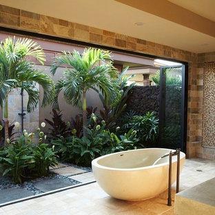 Immagine di una stanza da bagno tropicale con vasca freestanding e piastrelle a mosaico