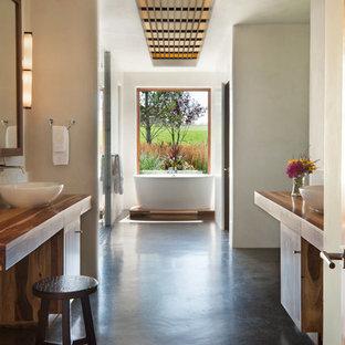 Свежая идея для дизайна: большая главная ванная комната в восточном стиле с настольной раковиной, столешницей из дерева, отдельно стоящей ванной, бежевыми стенами, фасадами островного типа, светлыми деревянными фасадами, двойным душем, раздельным унитазом, бетонным полом, серым полом, душем с распашными дверями, белой плиткой и коричневой столешницей - отличное фото интерьера