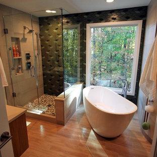 Стильный дизайн: главная ванная комната среднего размера в восточном стиле с плоскими фасадами, светлыми деревянными фасадами, японской ванной, угловым душем, унитазом-моноблоком, зеленой плиткой, керамогранитной плиткой, зелеными стенами, полом из керамогранита, настольной раковиной, столешницей из искусственного кварца, коричневым полом и душем с распашными дверями - последний тренд