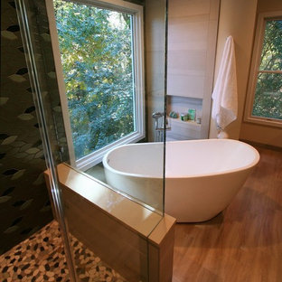 Example of a mid-sized master green tile and porcelain tile porcelain tile and brown floor bathroom design in DC Metro with flat-panel cabinets, light wood cabinets, a one-piece toilet, green walls, a vessel sink, quartz countertops and a hinged shower door