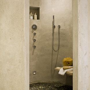 Modelo de cuarto de baño principal, de tamaño medio, sin sin inodoro, con armarios abiertos, bañera japonesa, sanitario de una pieza, baldosas y/o azulejos grises, paredes grises, suelo de baldosas tipo guijarro, lavabo de seno grande, suelo multicolor y ducha abierta
