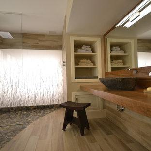Idee per una grande stanza da bagno padronale etnica con vasca giapponese, doccia a filo pavimento, piastrelle beige, piastrelle di ciottoli, pareti beige, lavabo a bacinella e top in legno