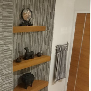 Ejemplo de cuarto de baño con ducha, asiático, de tamaño medio, con baldosas y/o azulejos blancas y negros, baldosas y/o azulejos de piedra, suelo de madera clara, bañera empotrada, combinación de ducha y bañera, sanitario de una pieza y paredes grises