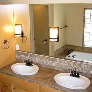 Immagine di una stanza da bagno padronale etnica di medie dimensioni con ante in stile shaker, ante in legno chiaro, vasca da incasso, WC monopezzo, piastrelle marroni, piastrelle grigie, piastrelle di ciottoli, pareti beige e lavabo da incasso
