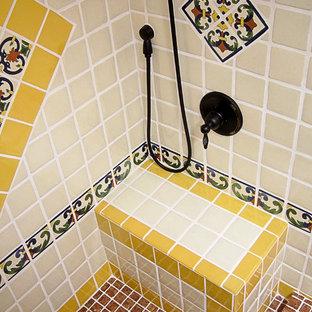 Inredning av ett amerikanskt mellanstort badrum med dusch, med luckor med upphöjd panel, skåp i ljust trä, en dusch i en alkov, en toalettstol med hel cisternkåpa, blå kakel, vit kakel, gul kakel, keramikplattor, vita väggar, tegelgolv, ett integrerad handfat, kaklad bänkskiva, rött golv och dusch med duschdraperi