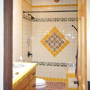 Ejemplo de cuarto de baño con ducha, de estilo americano, de tamaño medio, con armarios con paneles con relieve, puertas de armario de madera clara, ducha empotrada, sanitario de una pieza, baldosas y/o azulejos azules, baldosas y/o azulejos blancos, baldosas y/o azulejos amarillos, baldosas y/o azulejos de cerámica, paredes blancas, suelo de ladrillo, lavabo integrado, encimera de azulejos, suelo rojo y ducha con cortina