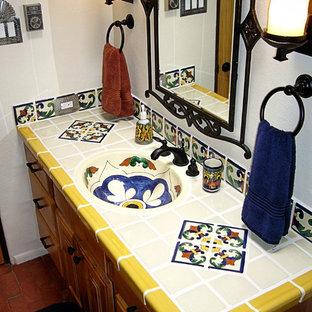 Ispirazione per una stanza da bagno con doccia chic di medie dimensioni con ante con bugna sagomata, ante in legno chiaro, doccia alcova, WC monopezzo, piastrelle blu, piastrelle bianche, piastrelle gialle, piastrelle in ceramica, pareti bianche, pavimento in mattoni, lavabo integrato, top piastrellato, pavimento rosso e doccia con tenda
