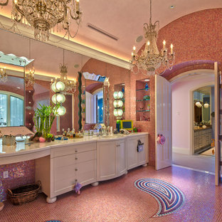 This is an example of a large eclectic master bathroom in Los Angeles with furniture-like cabinets, white cabinets, an alcove tub, a corner shower, pink tile, mosaic tile, pink walls, mosaic tile floors, an undermount sink, solid surface benchtops, pink floor and a hinged shower door.