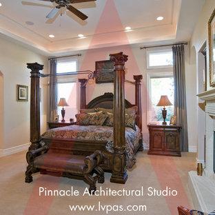 Imagen de dormitorio principal y abovedado, mediterráneo, extra grande, con paredes beige, suelo de madera en tonos medios, chimenea tradicional, marco de chimenea de hormigón y suelo marrón